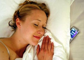 Woman sleeping with cell phone under pillow