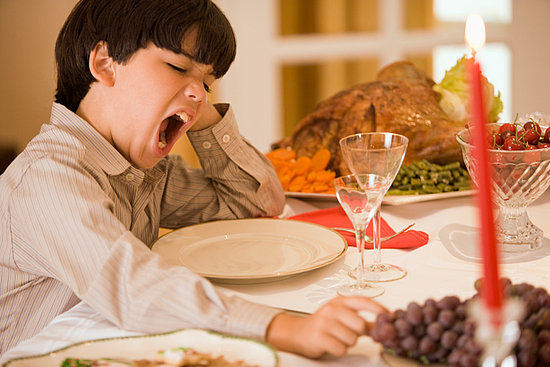Boy yawns and reaches for grape at large meal