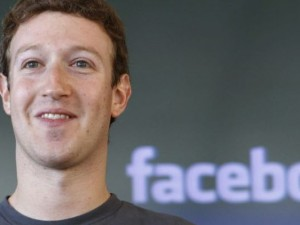 Mark Zuckerberg in front of Facebook emblem