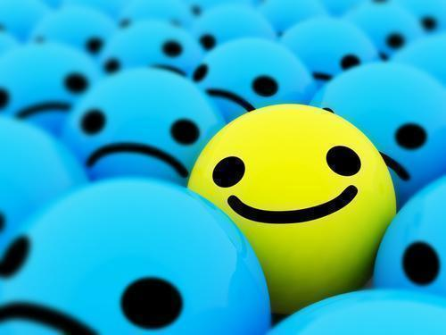 Happy smiling face among other sad smiley faces