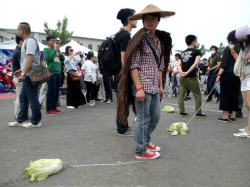 Chinese youth walks a cabbage on a leash