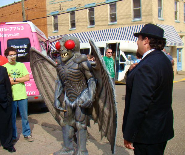 Attendees at the 2014 Mothman Festival dressed as The Mothman and Men in Black.