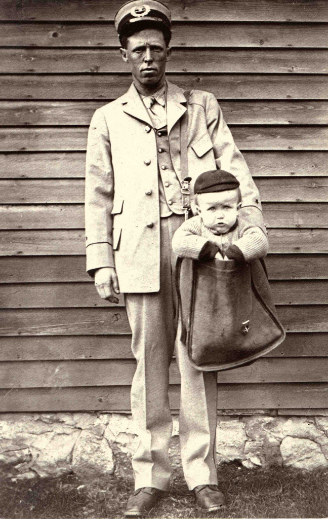 postal carrier holding a baby in a mail bag